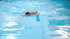 Ultrarapid av den muskulösa mannen som öva främre krypande i simbassäng stock video