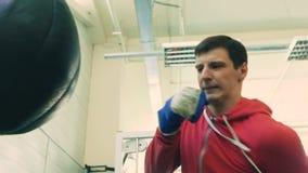 Ultrarapid av den unga boxaremannen som öva på en stansa påse i sportkonditionklubba lager videofilmer