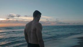 Ultrarapid av den unga idrottsmannen som går på stranden lager videofilmer