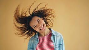 Ultrarapid av det tonåriga rörande huvudet för gullig afrikansk amerikan som vinkar lockigt hår arkivfilmer