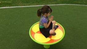 Ultrarapid av en flicka på en karusell i lekplatsen lager videofilmer