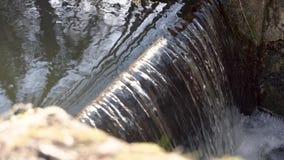 Ultrarapid av ett litet en liten fördämning för vattenbank med fallande vatten arkivfilmer