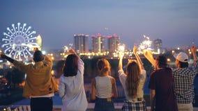 Ultrarapid av lyckliga ungdomvänner som rymmer tomtebloss och flyttning lyftta händer som står på taket som tycker om härlig sikt stock video