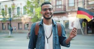 Ultrarapid av mellersta - östlig turist- hållande tysk flagga som ler utomhus stock video
