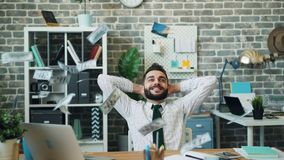 Ultrarapid av pengar som faller på lyckad affärsman i modernt kontor lager videofilmer