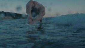 Ultrarapid av simmarebanhoppningen i vattnet som är utomhus- på solnedgång stock video