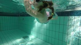 Ultrarapid av ung flickasimning som är undervattens- och gör en vridning arkivfilmer