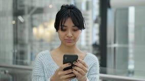 Ultrarapid för ståendepannaskott av det allvarliga asiatiska kvinnliga anseendet som skriver på telefonen lager videofilmer
