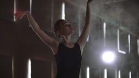 Ultrarapid: Flitig ung behagfull ballerina som dansar på beståndsdelar av klassisk balett i mörkret med ljus och rök arkivfilmer