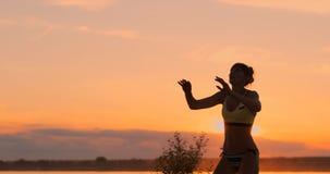ULTRARAPID LÅG VINKEL, SLUT UPP, SOLSIGNALLJUS: Idrotts- flicka som spelar hopp för strandvolleyboll i den luften och slagen lager videofilmer