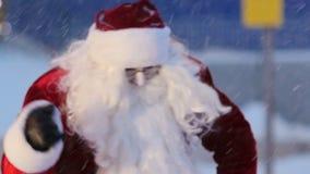 Ultrarapid Santa Claus har gyckel under snöfall i vinter att parkera stock video