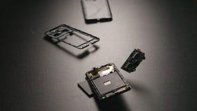 ULTRARAPID: Smartphone faller på ett golv, avbrott, och delar flyger bort stock video