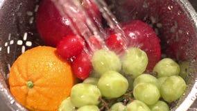 Ultrarapid som är nära upp av frukt som tvättar sig av vatten i en durkslag. lager videofilmer