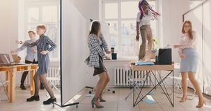 Ultrarapiddockaskottet, lyckliga multietniska kollegor dansar på det ljusa moderna kontorspartiet som tillsammans firar framgån arkivfilmer