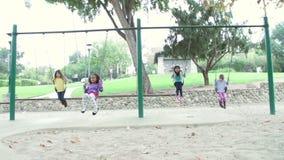 Ultrarapidföljd av fyra unga flickor som spelar på gungor arkivfilmer