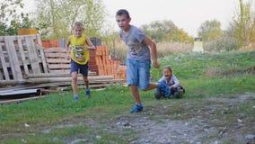 Ultrarapidgrupp av barn som spelar, kör och rider på det utomhus- leksakmedlet arkivfilmer