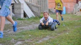 Ultrarapidgrupp av barn som spelar, kör och rider på det utomhus- leksakmedlet stock video