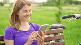 Ultrarapidkvinnan som smsar på mobiltelefonen parkerar in Använda hennes smartphone, messaging med att bläddra för vän lager videofilmer