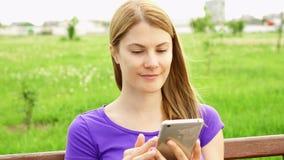 Ultrarapidkvinnan som smsar på mobiltelefonen parkerar in Använda hennes smartphone, messaging med att bläddra för vän arkivfilmer