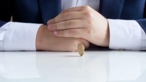Ultrarapidlängd i fot räknat av affärsmansammanträde bak kontorsskrivbordet och snurr ett mynt lager videofilmer