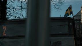 Ultrarapidlängd i fot räknat av en svensk flagga som överst svänger i vinden av en buss stock video