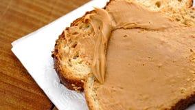 Ultrarapidmakro av fördelning av krämigt jordnötsmör på låg-carb rostat bröd