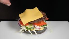 Ultrarapidmatbegrepp Kockdanandehamburgare N?rbild Process f?r matlagning f?r hamburgarerestaurangmeny Kocken förbereder snabbmat lager videofilmer