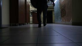Ultrarapidmideo av mannen som går till idrottshallen i den mörka korridoren arkivfilmer