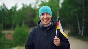 Ultrarapidportraif av den lyckliga invandrande stiliga mannen som vinkar den tyska flaggan, skrattar och ser kameran Världen stock video