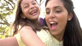 Ultrarapidskott av modern som på ryggen ger ritt för dotter stock video