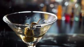 Ultrarapidskott av olivgrönt plaska in i martini arkivfilmer