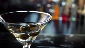 Ultrarapidskott av olivgrönt plaska in i martini lager videofilmer