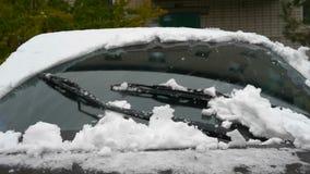 Ultrarapidskyttehänder som skrapar snö från den djupfrysta bilvindrutan, snöflingor som flödar över solen arkivfilmer