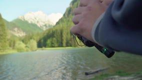 Ultrarapidslut upp av en man som rymmer en metspö och en rulle, eller sportfiskaren på en solig dag nära sjön Med berget och sjön arkivfilmer