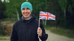 Ultrarapidstående av att le engelsmansportfanen som rymmer UK-flaggaflyg i vinden och ser kameran stock video