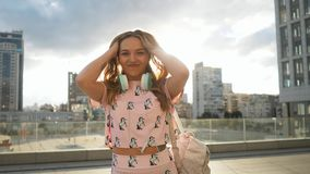 Ultrarapidstående av den attraktiva gulliga le unga kvinnan för Caucasian etnicitet med hörlurar och ryggsäcken i Urban stock video