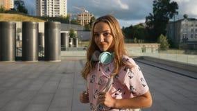 Ultrarapidstående av den attraktiva gulliga le unga kvinnan för Caucasian etnicitet med hörlurar och ryggsäcken i Urban arkivfilmer