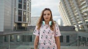 Ultrarapidstående av den attraktiva gulliga le unga kvinnan för Caucasian etnicitet med hörlurar och ryggsäcken i Urban lager videofilmer