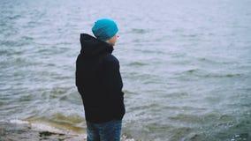 Ultrarapidstående av den fundersamma grabben i hatten, omslaget och jeans som står på havskusten och de hållande ögonen på vatten stock video