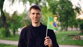 Ultrarapidstående av den glade flaggan och att le för ung man för handelsresande hållande brasilianska se kameran Nationellt symb arkivfilmer