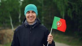 Ultrarapidstående av den glade turist- attraktiva unga grabben som vinkar den portugisiska flaggan med lyckligt leende och ser ka stock video