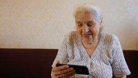 Ultrarapidstående av den lyckliga äldre kvinnan som talar vid den videopd sammanlänkningen på smartphonen och att le lager videofilmer