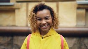 Ultrarapidstående av den lyckliga afrikansk amerikankvinnan med lockigt hår som ser kameran och ler därefter att skratta lager videofilmer