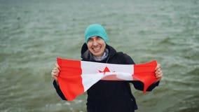 Ultrarapidstående av den lyckliga unga mannen som rymmer den stora textilflaggan av Kanada, ser kameran och ler med vatten stock video
