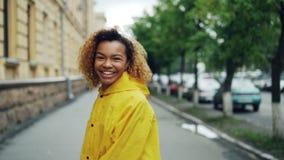 Ultrarapidstående av den nätta afrikansk amerikanstudenten för ung kvinna som går i gatan, vänder och ser kameran stock video