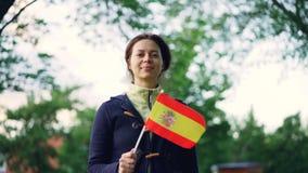 Ultrarapidstående av den nätta spanjorfanen för ung kvinna som vinkar den officiella flaggan av Spanien och ser kameran med trevl lager videofilmer