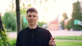 Ultrarapidstående av den vinkande nationsflaggan för amerikansk man av USA och att le och se kameran Ungdomarsom är lyckliga stock video