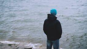Ultrarapidstående av det turist- anseendet för ung man på havskusten och att se vågor på kall blåsig dag folk arkivfilmer