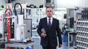 Ultrarapidstående av företagsägaren i fabrik som går in mot kamera arkivfilmer