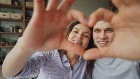 Ultrarapidstående av lycklig multietnisk pardanandehjärta med deras händer som ser kameran och att le romantiker stock video